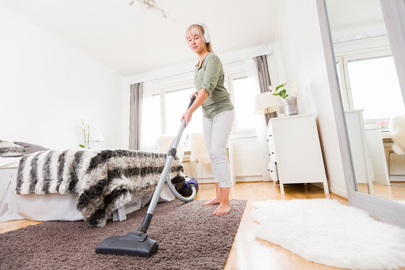 Young woman vacuuming floor